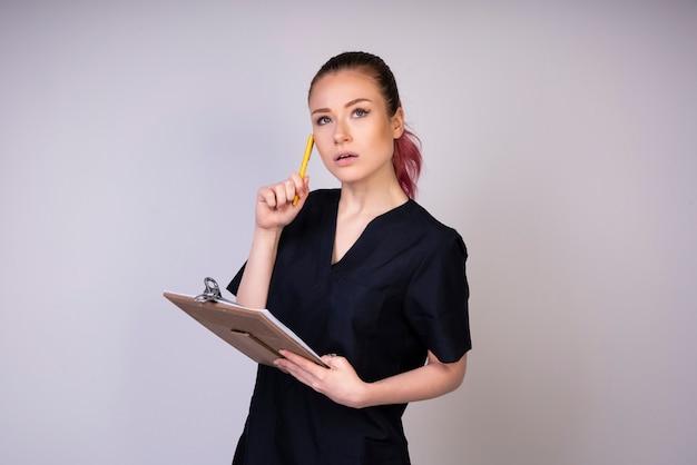 Menina de pensamento em uniforme médico