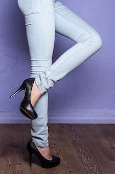 Menina de pernas compridas em sapatos pretos com salto alto no chão de madeira levantando uma perna