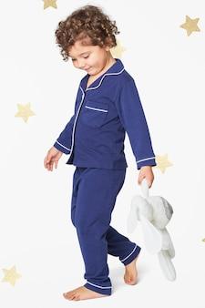 Menina de pijama azul com um coelhinho de pelúcia