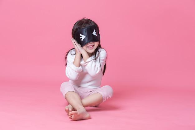 Menina de pijama branco e máscara preta, sentado no quarto rosa na hora de dormir.