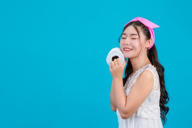 Menina de pijama branco, segurando um rolo de papel na mão no azul.