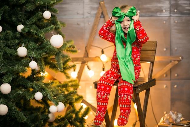 Menina de pijama na árvore de natal em uma cadeira de madeira