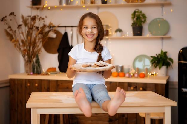 Menina de pijama na cozinha com biscoitos