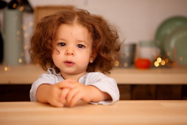Menina de pijama na cozinha de natal