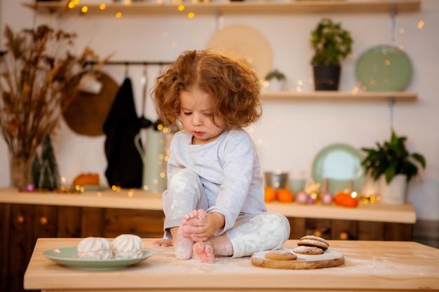 Menina de pijama na cozinha
