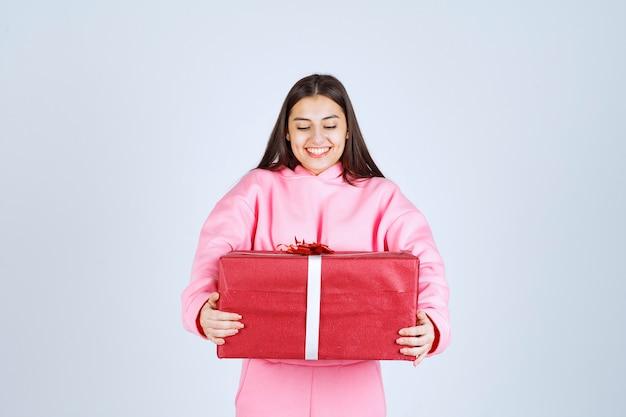 Menina de pijama rosa abraçando uma grande caixa vermelha de presente e sorrindo.