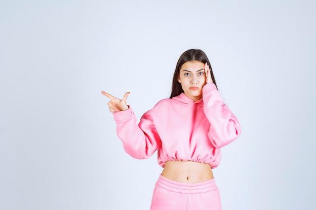 Menina de pijama rosa apontando para algo à esquerda