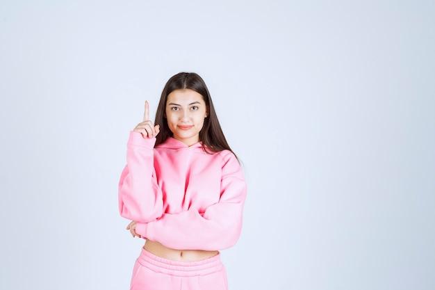 Menina de pijama rosa apontando para algum lugar.