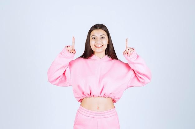 Menina de pijama rosa apontando para o andar de cima com cara emocionada