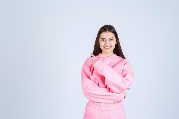 Menina de pijama rosa apontando para o lado esquerdo