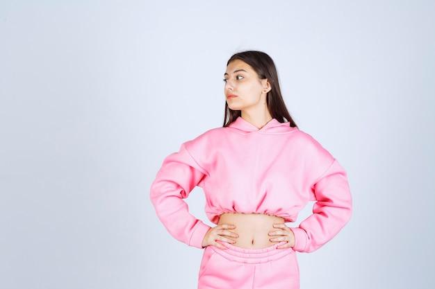 Menina de pijama rosa fazendo poses insatisfeitas e neutras