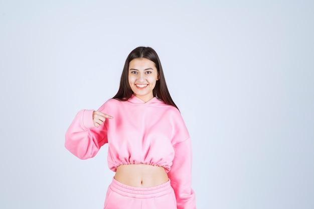 Menina de pijama rosa fazendo poses positivas e desagradáveis