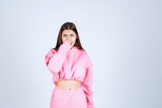 Menina de pijama rosa parece chocada e apavorada