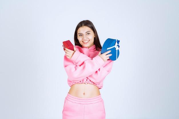 Menina de pijama rosa segurando caixas de presente da forma de coração vermelho e azul com as duas mãos.
