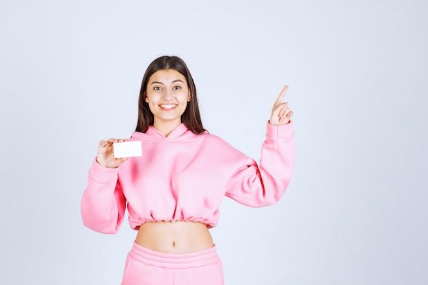 Menina de pijama rosa segurando um cartão de visita e apontando para outra pessoa.