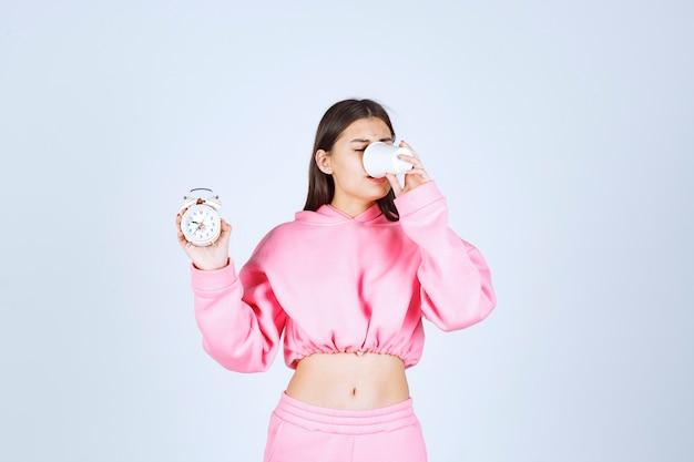 Menina de pijama rosa segurando um despertador e bebendo uma xícara de café.