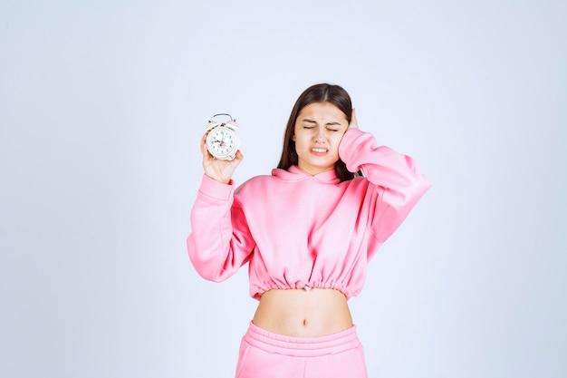 Menina de pijama rosa segurando um despertador e fica incomodada por causa do barulho.