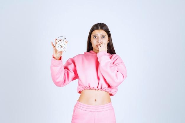 Menina de pijama rosa segurando um despertador e percebendo que está atrasada.