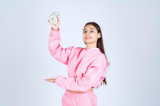 Menina de pijama rosa segurando um despertador e promovendo-o como um produto.
