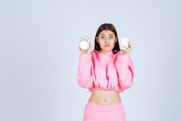 Menina de pijama rosa segurando um despertador e uma xícara de café com uma cara cansada.