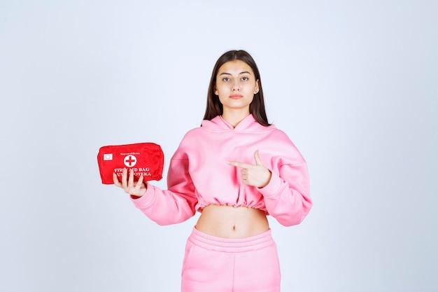 Menina de pijama rosa segurando um kit de primeiros socorros vermelho e promovendo-o.