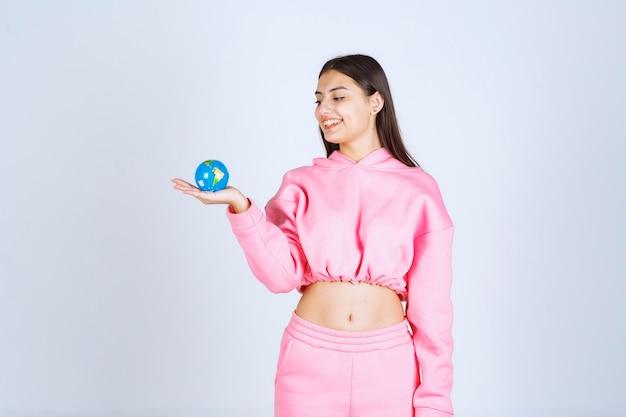 Menina de pijama rosa, segurando um mini globo na mão.