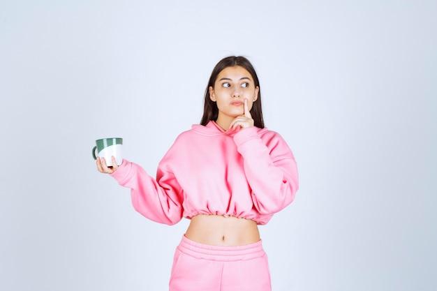 Menina de pijama rosa segurando uma caneca de café e parece em dúvida.