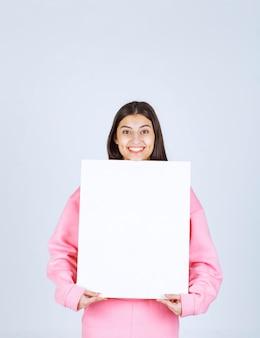 Menina de pijama rosa, segurando uma placa de apresentação quadrada em branco na frente dela.