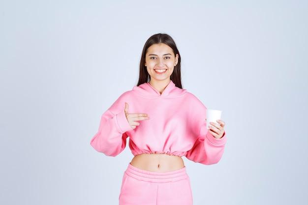 Menina de pijama rosa segurando uma xícara de café e apontando para algo