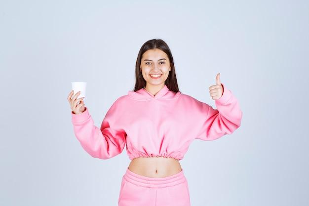 Menina de pijama rosa segurando uma xícara de café e apreciando o sabor