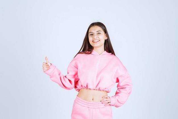 Menina de pijama rosa, sorrindo e curtindo algo.