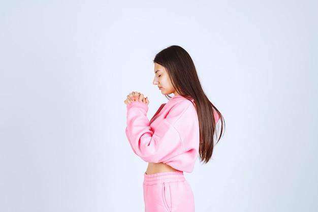 Menina de pijama rosa unindo as mãos e orando