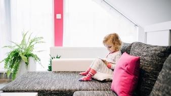 Menina de pijama usando tablet no sofá