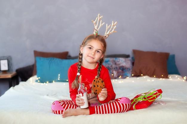 Menina de pijama vermelho senta-se com leite e biscoitos na véspera de natal e aguarda o papai noel. criança come biscoitos com leite em casa. menina vestida como um chifre de veado. feliz natal, ano novo