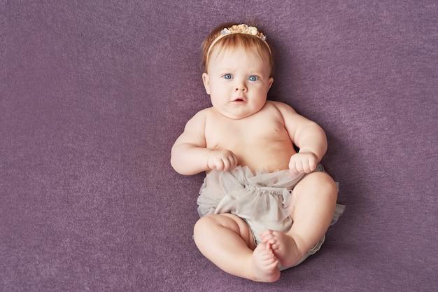 Menina de quatro meses encontra-se em uma parede roxa