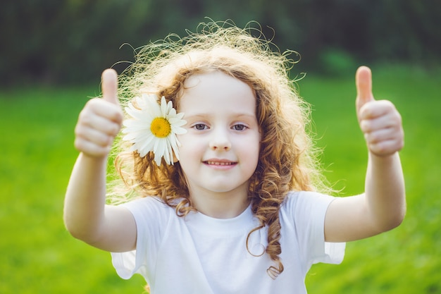 Menina de riso com a margarida em seus cabelos, mostrando os polegares acima.