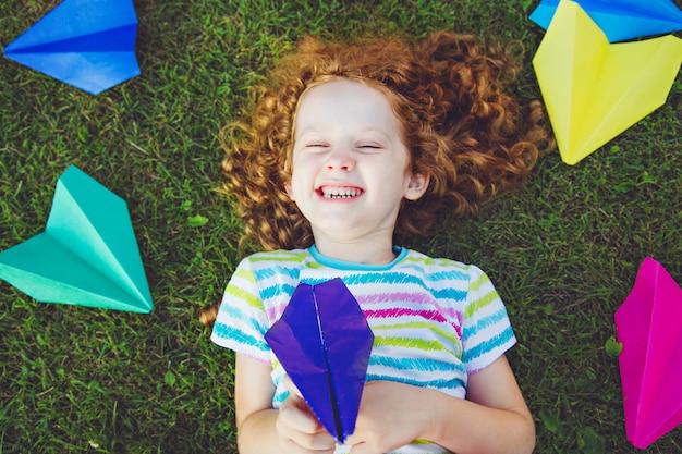 Menina de riso com o avião de papel em sua mão no gramado verde.