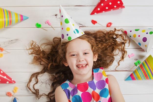 Menina de riso feliz na festa de anos que encontra-se no assoalho de madeira.