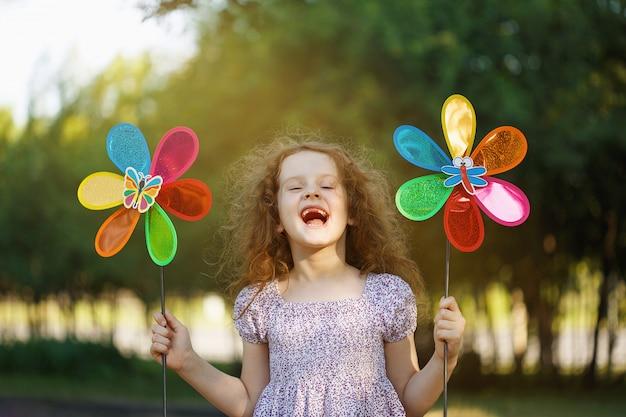 Menina de riso que guarda brinquedos de um pinwheel do arco-íris.