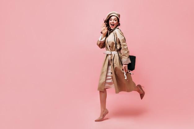 Menina de sobretudo e boina alegremente acenando com a mão e correndo sobre fundo rosa.