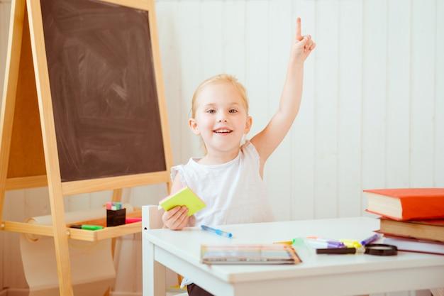 Menina de sorriso adorável que faz trabalhos de casa e que aponta acima com dedo.