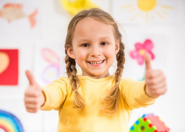 Menina de sorriso bonita no pulôver amarelo que faz os polegares acima.