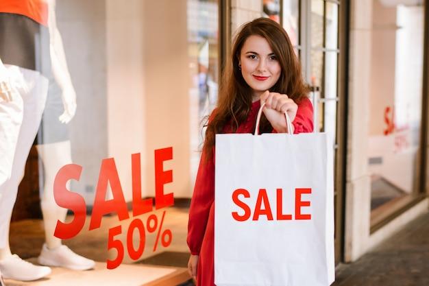 Menina de sorriso bonita no vestido vermelho que está com saco branco ao comprar. venda de inscrição 50% na superfície da janela de uma loja em segundo plano