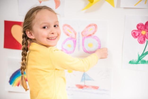 Menina de sorriso bonita pequena no pulôver amarelo.