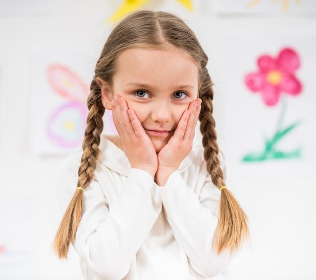 Menina de sorriso bonita pequena no pulôver branco em casa.