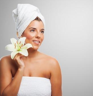 Menina de sorriso com a toalha na cabeça que prende o lírio