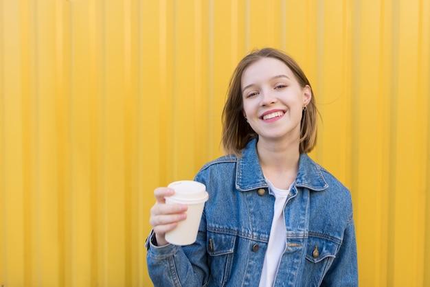 Menina de sorriso com a xícara de café em suas mãos contra o fundo da parede amarela.