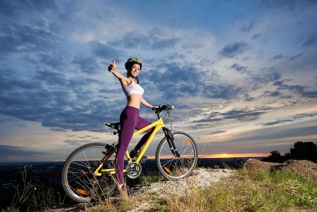 Menina de sorriso com bicicleta que sorri e que mostra o polegar.