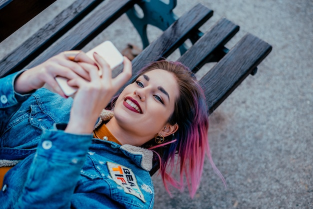 Menina de sorriso com o cabelo roxo que encontra-se em um banco, usando o telefone.