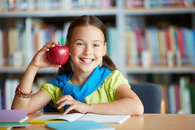 Menina de sorriso com uma maçã